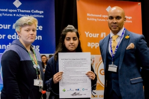 Principal Robin Ghurbhurun stands with students Isaac and Alina to display the signed plastic reduction pledge