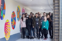 Students proudly stand with the mural they painted